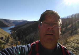 Tim Bondy with Anderson Ranch Reservoir in the background while hiking up to Wilson Flat in southern Idaho.